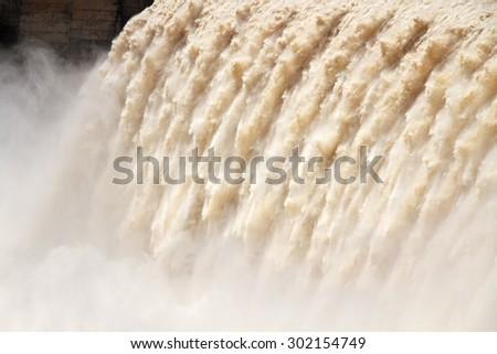 Strong flowing water with water spray from the open sluice gates of a large dam  - stock photo