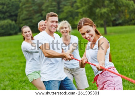 Strong group in a competition playing tug of war - stock photo