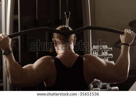 Strong guy training back muscles using equipment