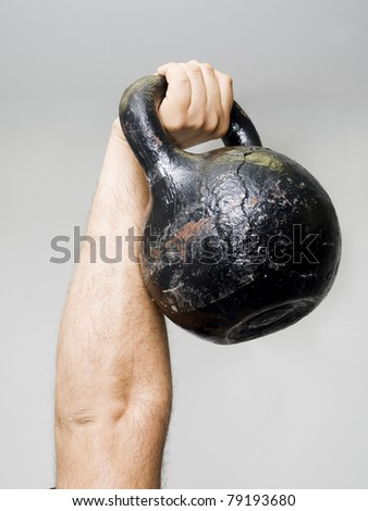 Strong hand up with dumbbell on gray background - stock photo