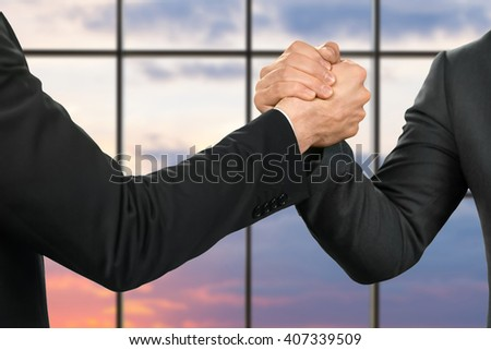 Strong handshake of businessmen. Friends' greeting on sunrise background. Partnership and protection. Strength of a gesture. - stock photo