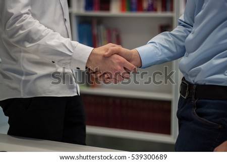 Strong handshake of two men after finished job on a project in a corporate startup company with books on the bookshelf in the background.