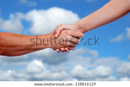 Strong handshake with a nice blue sky background - stock photo