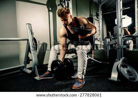 strong handsome bodybuilder athlete works out and pumping with heavy  dumbbells in gym - stock photo