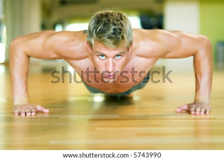Strong, handsome man doing push-ups - stock photo