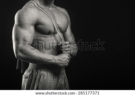 Strong, healthy man posing on a black background. Bodybuilder. The concept of a healthy diet and a healthy lifestyle.