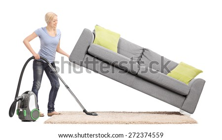 Strong housewife lifting a sofa with one hand and vacuuming underneath it isolated on white background - stock photo