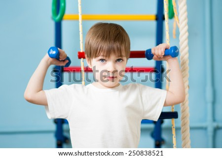Strong kid boy exercising with dumbbells. Healthy life, sport. - stock photo