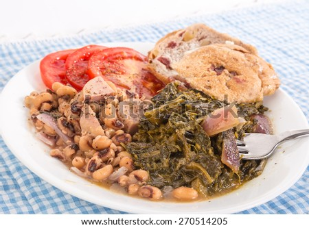 Strong light from upper right on collard greens seasoned with salt pork and red onions and black-eyed peas with chunks of spam.  Blue gingham tablecloth emphasizes country kitchen feel. - stock photo