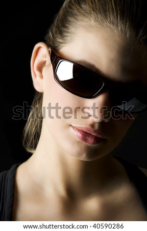 strong light studio shot of beautiful blond woman with black sunglasses