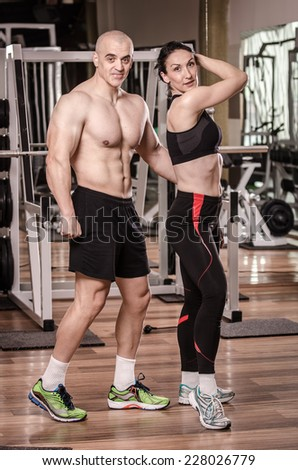 Strong man and a woman posing in a gym , showing their biceps  - stock photo