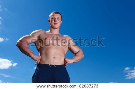 Strong man athlete outdoor with blue sky - stock photo