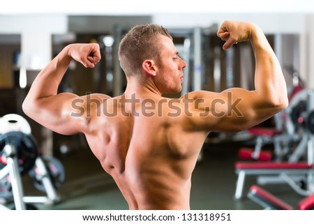 Strong man, bodybuilder posing in Gym, workout equipment in the background - stock photo