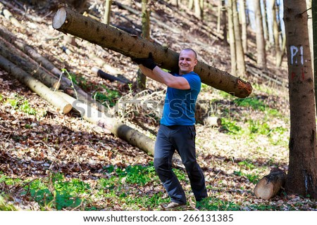 strong man carrying a tree trunk - stock photo