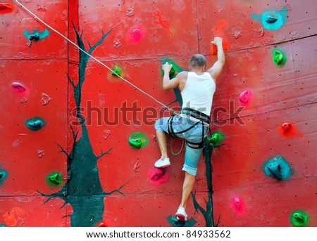 strong man climbing on a climbing wall training in insurance - stock photo