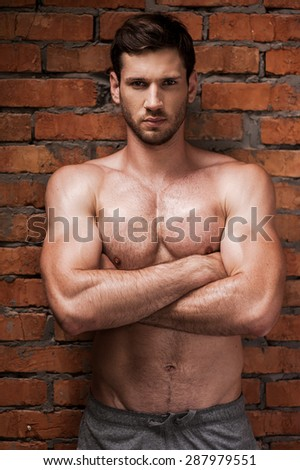 Strong man. Confident young muscular man keeping arms crossed and looking at camera while standing against brick wall  - stock photo
