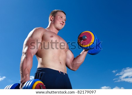 Strong man doing exercises outdoor with dumbbells - stock photo