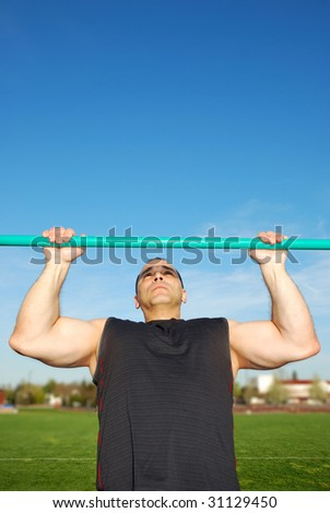 Strong man doing pull ups on a bar in a field with blue sky in the background. - stock photo