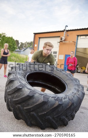 Strong man flips heavy tire outdoor as workout - stock photo