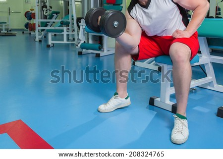 Strong man holding a dumbbell in the gym. Man doing exercise with dumbbell. Gym, weights, muscles, sports, strength. - The concept of a healthy lifestyle. Article about the sport and health. - stock photo