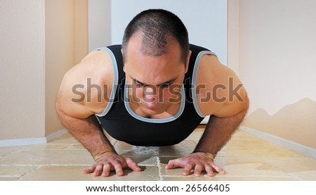 Strong man in tank top doing push ups on the floor. - stock photo
