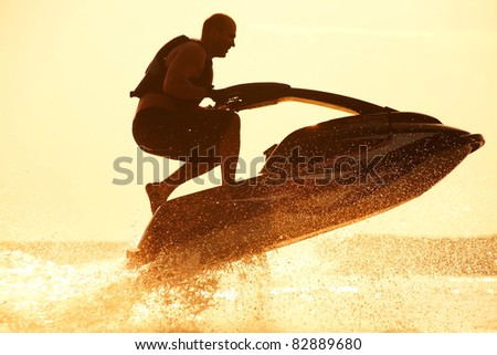 strong man jumps on the jetski above the water at sunset .silhouette spray. - stock photo