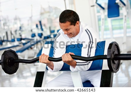 Strong man lifting some weights at the gym - stock photo