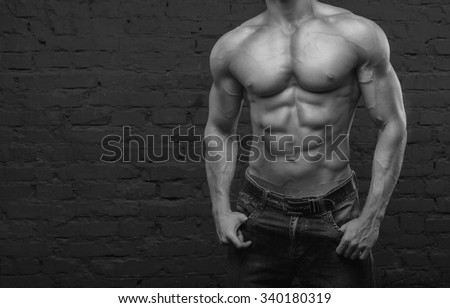 Strong man. Muscular male body. Bodybuilder. Black and white image. Copy space for text. Posters, advertising for gym. Muscular man on dark background brick wall. Athletic man. Fitness muscular body. - stock photo