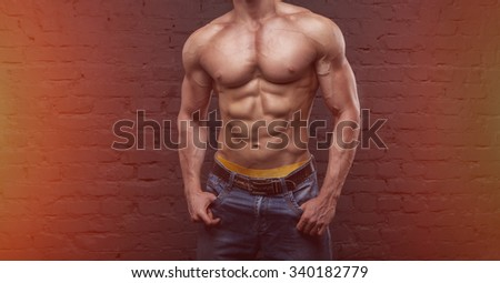 Strong man. Muscular male body. Bodybuilder. Copy space for text. Posters, advertising for gym. Muscular man on dark background brick wall. Athletic man. Fitness muscular body. new sports year - stock photo