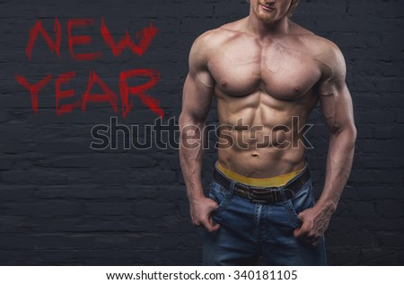 Strong man. Muscular male body. Bodybuilder. New Year - concept. Copy space for text. Posters, advertising for gym. Muscular man on dark background brick wall. Athletic man. Fitness muscular body. - stock photo