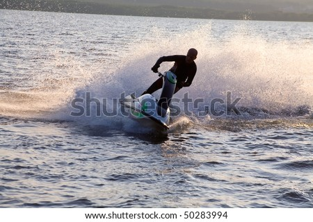 strong man riding on jet skis in the sea at sunset.  silhouette