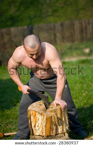 Strong man splitting wood with an axe in the countryside