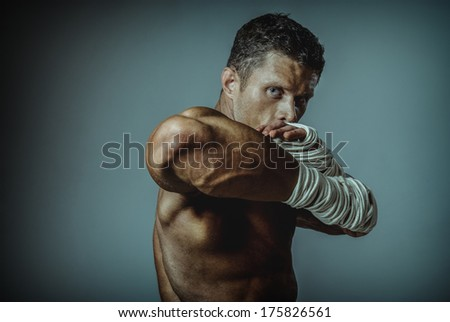Strong man street fighter, by the hand wound rope. Masculine man defender. - stock photo