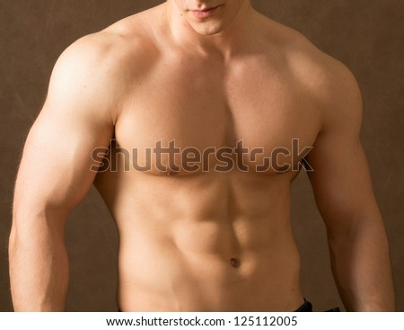 Strong man with a helathy body isolated over beige background - stock photo