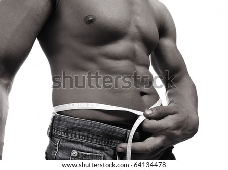 Strong man with a helthy body measuring his stomach, diet concept, isolated
