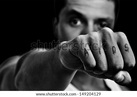 Strong man with a tattoo in the punch, written AIDS. Concept of fight AIDS or stop AIDS. In Black and White. - stock photo
