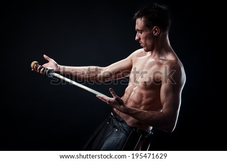 Strong man with ancient sword on the black background - stock photo