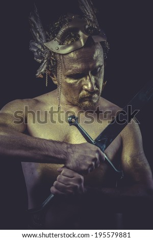 Strong man with body painted gold feather mask and steel sword - stock photo