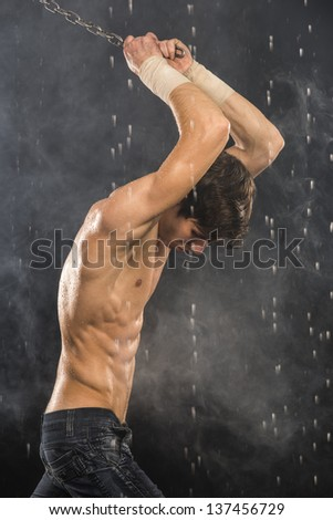 Strong man with chains in aqua studio - stock photo