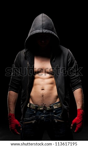 strong man with red bandage on hands standing in dark - stock photo