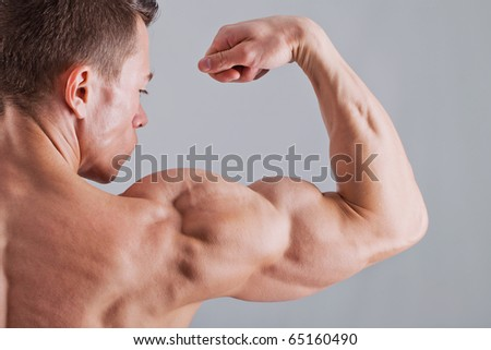 Strong man with relief body - stock photo