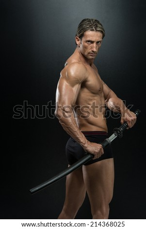 Strong Man With Samurai Sword - Portrait Of A Handsome Muscular Ancient Warrior With A Sword - stock photo
