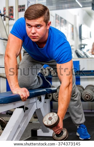 Strong man working with  dumbbells his body at gym.