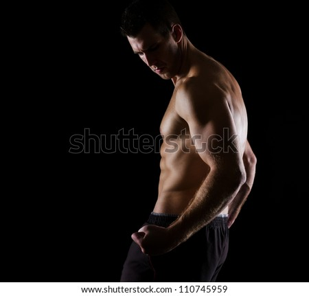 Strong muscular athlete posing on black - stock photo