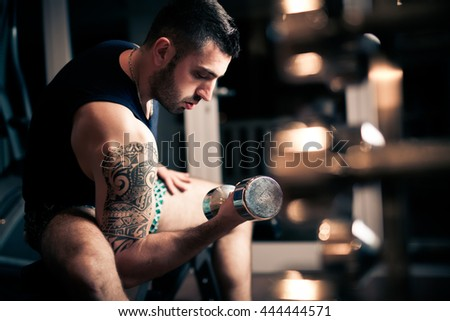 Strong muscular bodybuilder doing exercise with dumbbell in the gym. Part of fitness body. Sports and fitness.Fitness man in the gym.Strong man at the gym lifting weights.Low key - stock photo