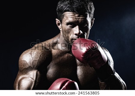 Strong muscular boxer in red boxing gloves. A man in a boxing stand.