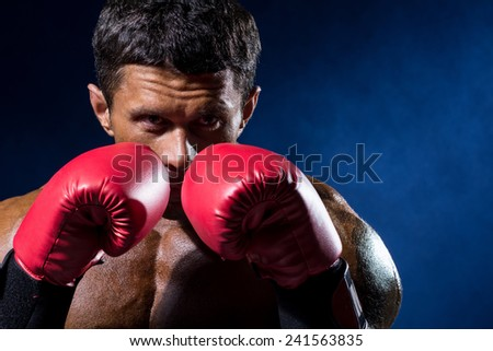 Strong muscular boxer in red boxing gloves on a blue background. A man in a boxing stand - stock photo
