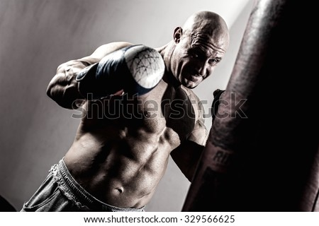 Strong muscular boxer in training. Athlete with boxing pear