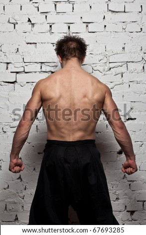 Strong muscular man back at  white wall background - stock photo