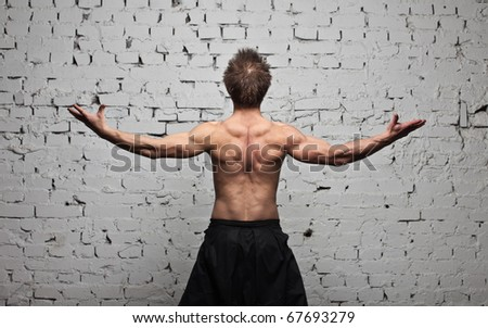 Strong muscular man back at  white wall background in flying and free standing - stock photo